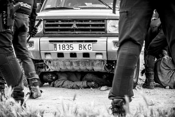 Fotografía de Jesús Blasco de Avellaneda para Nthephoto. Un inmigrante subsahariano acaba de acceder a Melilla saltando el vallado fronterizo y se esconde bajo un vehículo para que las fuerzas españolas no lo expulsen a Marruecos