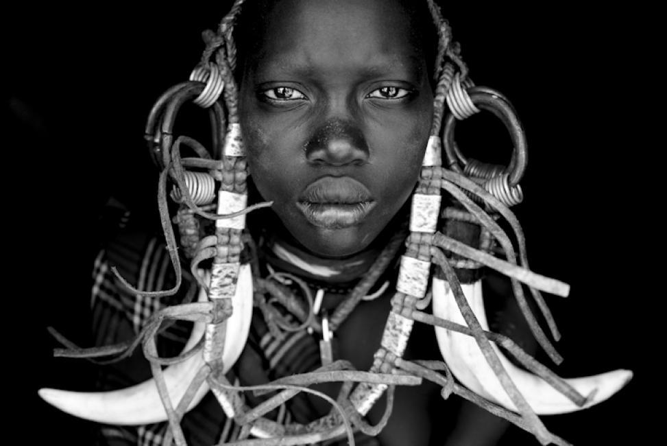 Fotografía de Enrique López-Tapia de Inés para Nthephoto. Una joven mursi en el interior de su choza, mostrando sus adornos tradicionales. Valle del Omo, Etiopía.